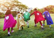 Niños alegres de los super héroes que expresan concepto de la positividad Imagenes de archivo