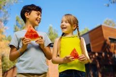 Niños alegres que comen una sandía madura Imagen de archivo libre de regalías