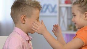 Niños alegres que engañan alrededor, muchacho que hace caras para entretener a la muchacha, divirtiéndose metrajes