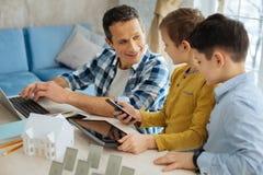 Niños alegres que hacen preguntas acerca de los dispositivos de los padres Imágenes de archivo libres de regalías