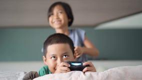 Niños alegres que juegan al videojuego en dormitorio almacen de video