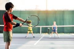 Niños alegres que juegan a tenis en corte Foto de archivo libre de regalías