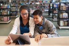Niños alegres que miran la tableta en biblioteca fotografía de archivo