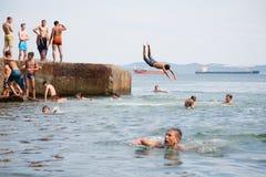 Niños alegres que saltan y que se zambullen en el mar del muelle viejo Fotografía de archivo