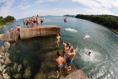 Niños alegres que saltan y que se zambullen en el mar del muelle viejo Imagenes de archivo