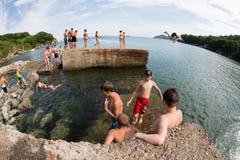 Niños alegres que saltan y que se zambullen en el mar del muelle viejo Fotos de archivo libres de regalías
