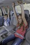 Niños alegres que se sientan en el asiento trasero del coche Imagen de archivo