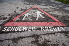 Niños alemanes que cruzan la señal de tráfico de la acera de la muestra Asphalt Deta Foto de archivo