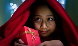 Niños asiáticos con la caja de regalo debajo de la manta Fotografía de archivo libre de regalías