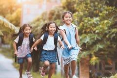 Niños asiáticos del alumno con el funcionamiento de la mochila Imagenes de archivo