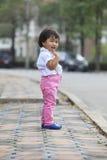 Niños asiáticos del niño que se colocan al lado del camino de la calle con emo relajante Imagen de archivo