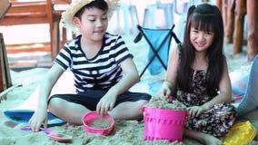 Niños asiáticos felices que juegan la arena en la playa metrajes