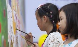 Niños asiáticos que dibujan imágenes y que escriben sus deseos Fotos de archivo libres de regalías