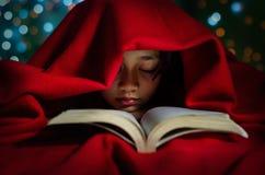 Niños asiáticos que duermen con el libro en la cama Imagenes de archivo