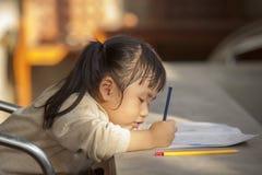 Niños asiáticos que hacen el trabajo del hogar de la escuela Imagen de archivo libre de regalías
