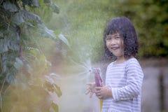 Niños asiáticos que juegan el agua que salpica el frome una manguera con happine Imágenes de archivo libres de regalías
