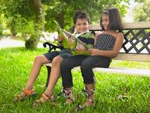 Niños asiáticos que leen en el parque Fotografía de archivo libre de regalías