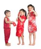 Niños asiáticos que miran a escondidas en el paquete rojo Fotografía de archivo