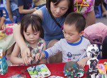 Niños asiáticos que pintan y que escriben sus deseos en desear tarjetas Fotos de archivo libres de regalías