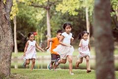 Niños asiáticos que se divierten a correr y a jugar junto Imágenes de archivo libres de regalías