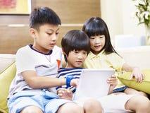 Niños asiáticos que usan la tableta digital junto Imagen de archivo libre de regalías