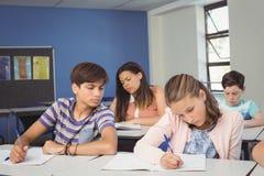 Niños atentos de la escuela que hacen la preparación en sala de clase Imagenes de archivo