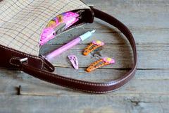 Niños bolso y accesorios en la tabla de madera Pequeño bolso, cuaderno, pluma rosada, pinzas de pelo brillantes para la muchacha Imagen de archivo