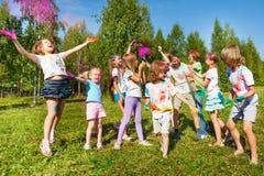 Niños brillantes y felices que juegan con el polvo coloreado Fotos de archivo libres de regalías