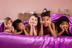 Niños cansados sonrientes en cama Foto de archivo