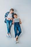 Niños casuales sonrientes usando los dispositivos digitales mientras que miente en el piso Imágenes de archivo libres de regalías
