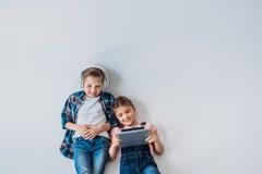 Niños casuales sonrientes usando los dispositivos digitales mientras que miente en el piso Fotos de archivo
