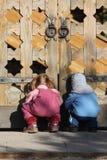 Niños cerca de las puertas de madera fotos de archivo