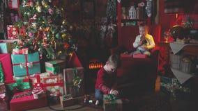 Niños cerca del árbol de navidad con los regalos para abrir sus regalos de la Navidad metrajes