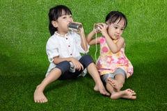 Niños chinos asiáticos que juegan con Tin Can Phone Foto de archivo