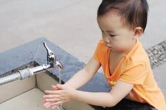 Niños chinos que lavan la mano. Imagenes de archivo