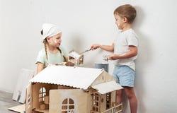 Niños como adultos: Un muchacho y una muchacha pintar una casa de muñecas blanca y conseguir sucio con la pintura Foto auténtica imágenes de archivo libres de regalías