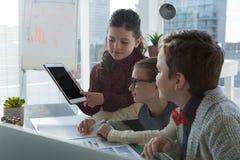 Niños como discusión de los ejecutivos de operaciones sobre la tableta digital Foto de archivo libre de regalías