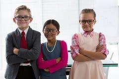Niños como ejecutivo de operaciones que sonríe mientras que se coloca en la oficina Fotos de archivo