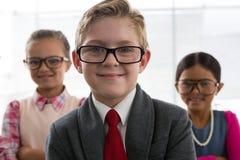Niños como ejecutivo de operaciones que sonríe mientras que se coloca en la oficina Fotografía de archivo libre de regalías