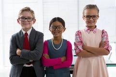 Niños como ejecutivo de operaciones que sonríe mientras que se coloca en la oficina Fotos de archivo libres de regalías