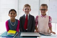 Niños como ejecutivo de operaciones que sonríe mientras que se coloca en la oficina Foto de archivo libre de regalías