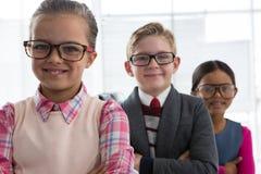Niños como ejecutivo de operaciones que sonríe mientras que se coloca en la oficina Foto de archivo