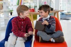 Niños como ejecutivos de operaciones que obran recíprocamente mientras que usa la tableta digital Fotos de archivo libres de regalías