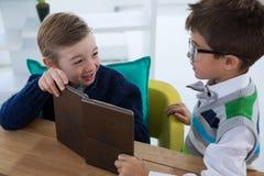 Niños como ejecutivos de operaciones que obran recíprocamente mientras que usa la tableta digital Fotografía de archivo libre de regalías
