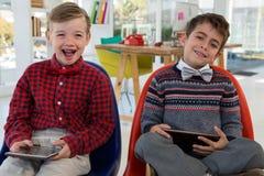 Niños como ejecutivos de operaciones que sostienen la tableta digital mientras que se sienta Foto de archivo libre de regalías