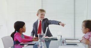 Niños como ejecutivos de operaciones que tienen una reunión en la sala de juntas 4k metrajes