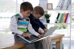 Niños como ejecutivos de operaciones que usan el ordenador portátil mientras que se sienta en la tabla Imagen de archivo