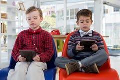 Niños como ejecutivos de operaciones que usan la tableta digital mientras que se sienta Imagenes de archivo