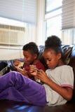 Niños con dieta de los pobres que comen la comida en Sofa At Home Foto de archivo libre de regalías