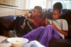 Niños con dieta de los pobres que comen la comida en Sofa At Home Fotos de archivo